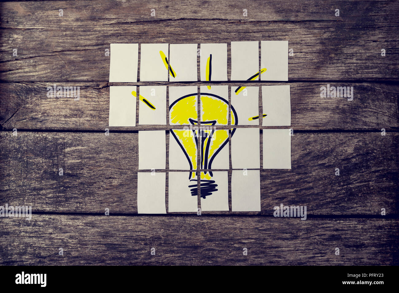 Top view of hand drawn yellow light bulb assembled with many cards over textured rustic boards with a retro faded effect. Conceptual of innovation, re Stock Photo