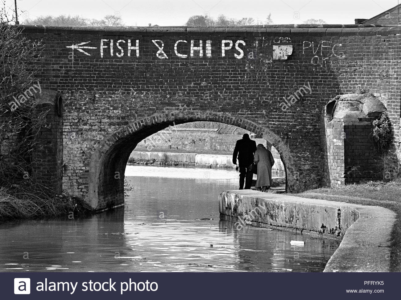 An old couple duck down to walk beneath a bridge on the towpath of the Caldon Canal in Stoke-on-Trent, Staffordshire, UK - Stock Image