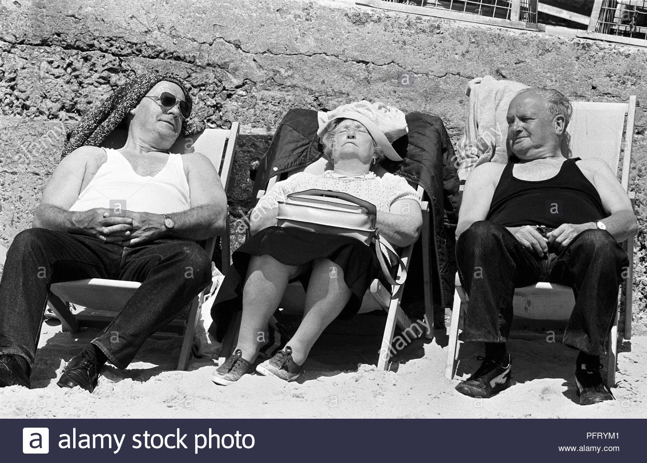 Two elderly men, sat in deckchairs either side of an elderly lady, watch her and smile as she snoozes in the afternoon sunshine on the beach at Tenby, Wales. Vintage black and white photograph first published The Sunday Times - Stock Image