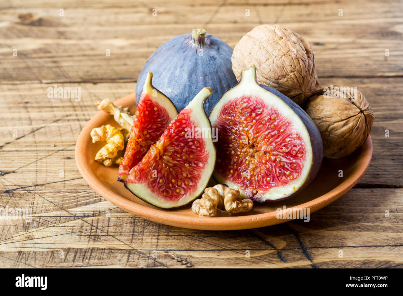 Fresh figs whole and cut kernels of walnuts on a plate the old wooden background - Stock Image