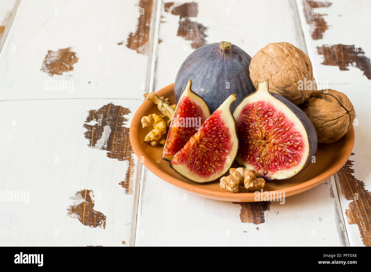 Fig walnuts cinnamon anise on a plate of old wooden background - Stock Image