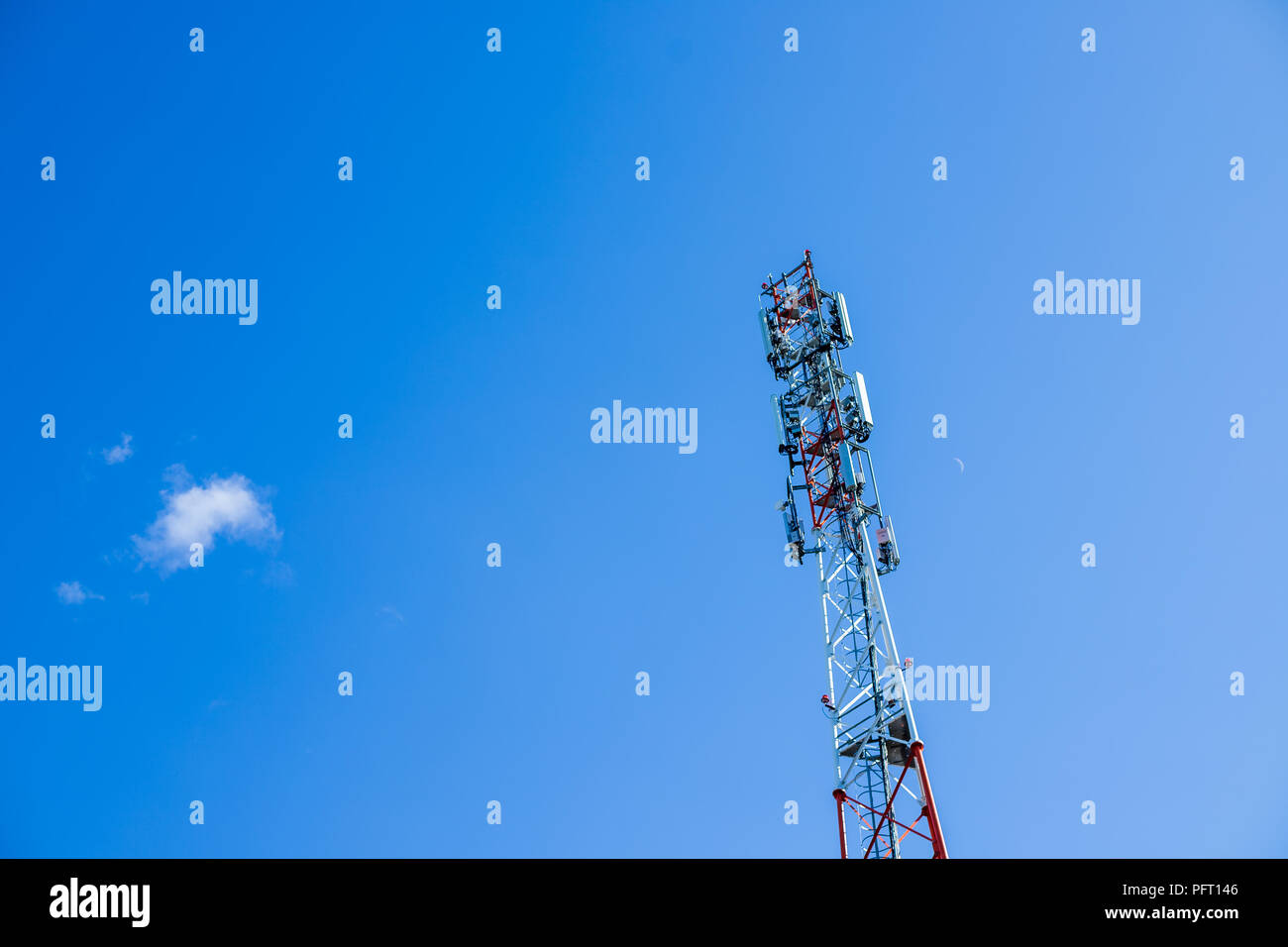 Mobile phone Telecommunication Radio antenna Tower. Cell phone tower.phone base station with TV and wireless internet antennas.Copy space.Huge communication antenna tower and satellite dishes against blue sky. - Stock Image