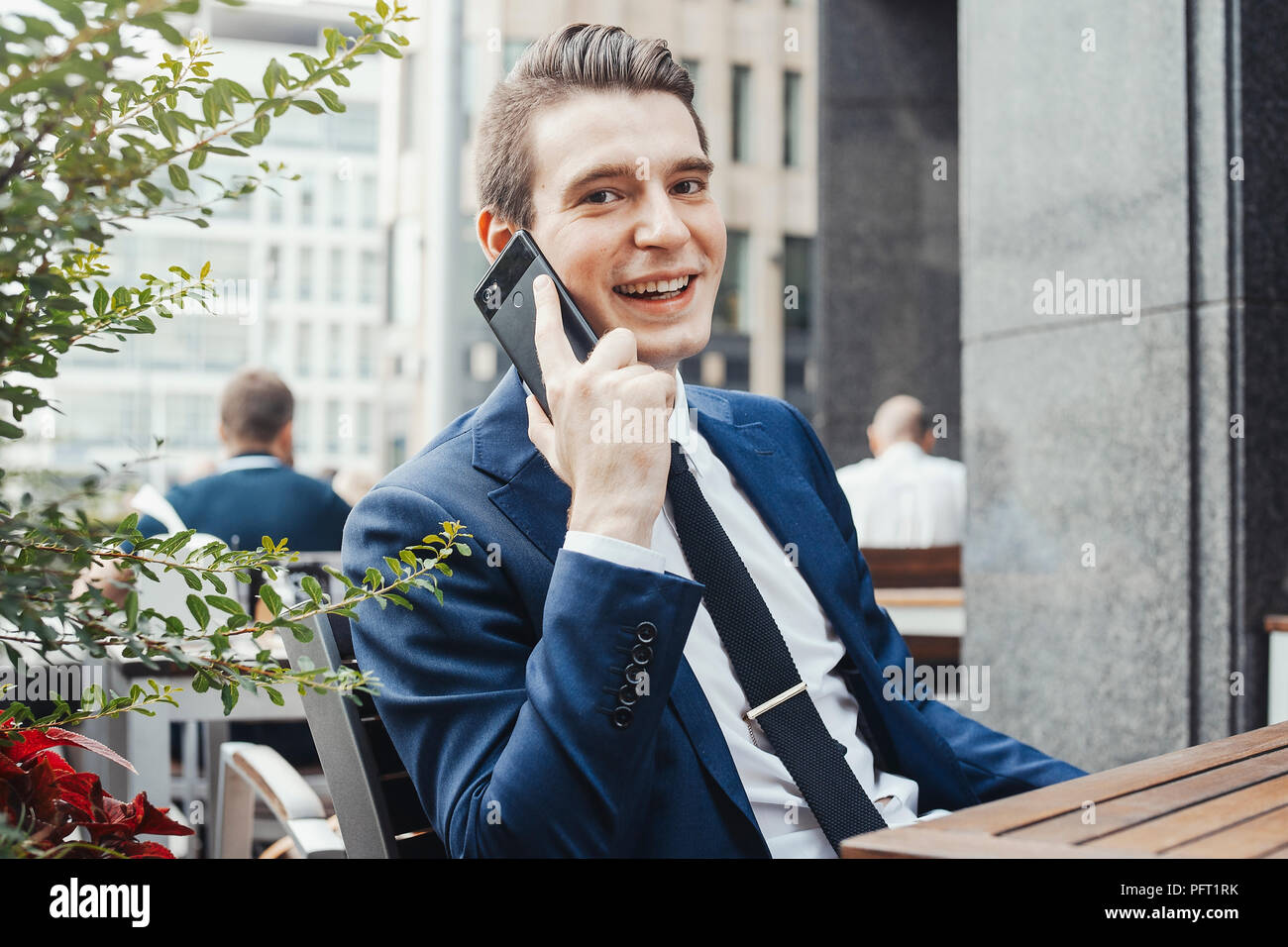 Young attractive businessman talking by mobile phone and looking at viewer. - Stock Image