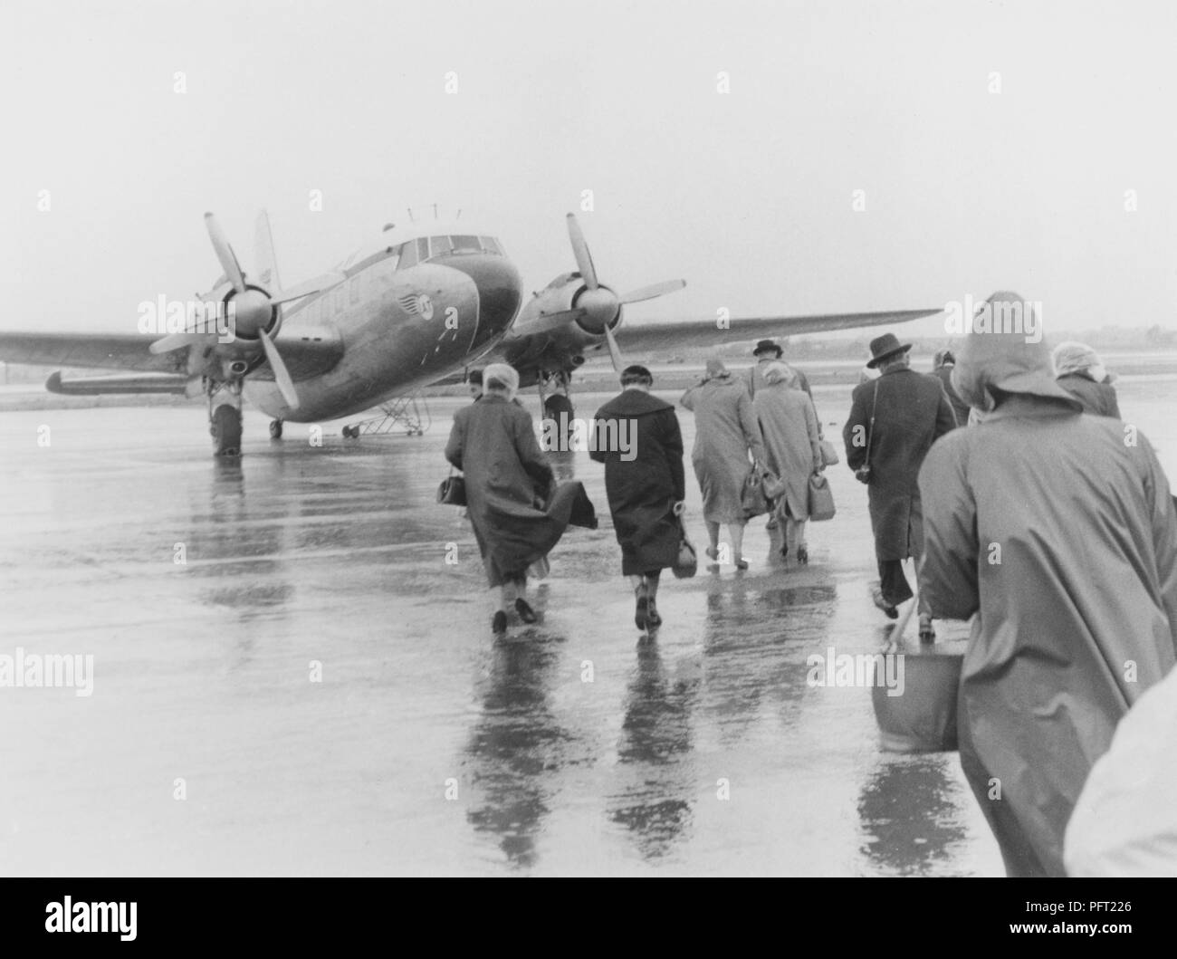 1950s vacation. A group of people are walking in the pouring rain towards the waiting plane bound for Spain. Sweden 1951. ref 385 - Stock Image