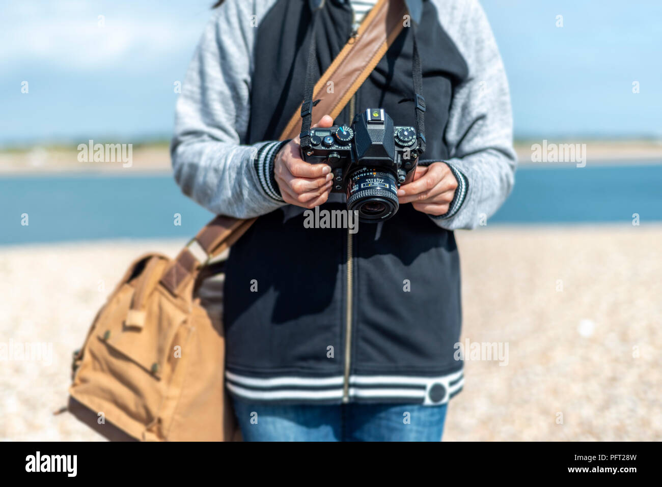 woman holding a retro camera. Close up, waist up. - Stock Image