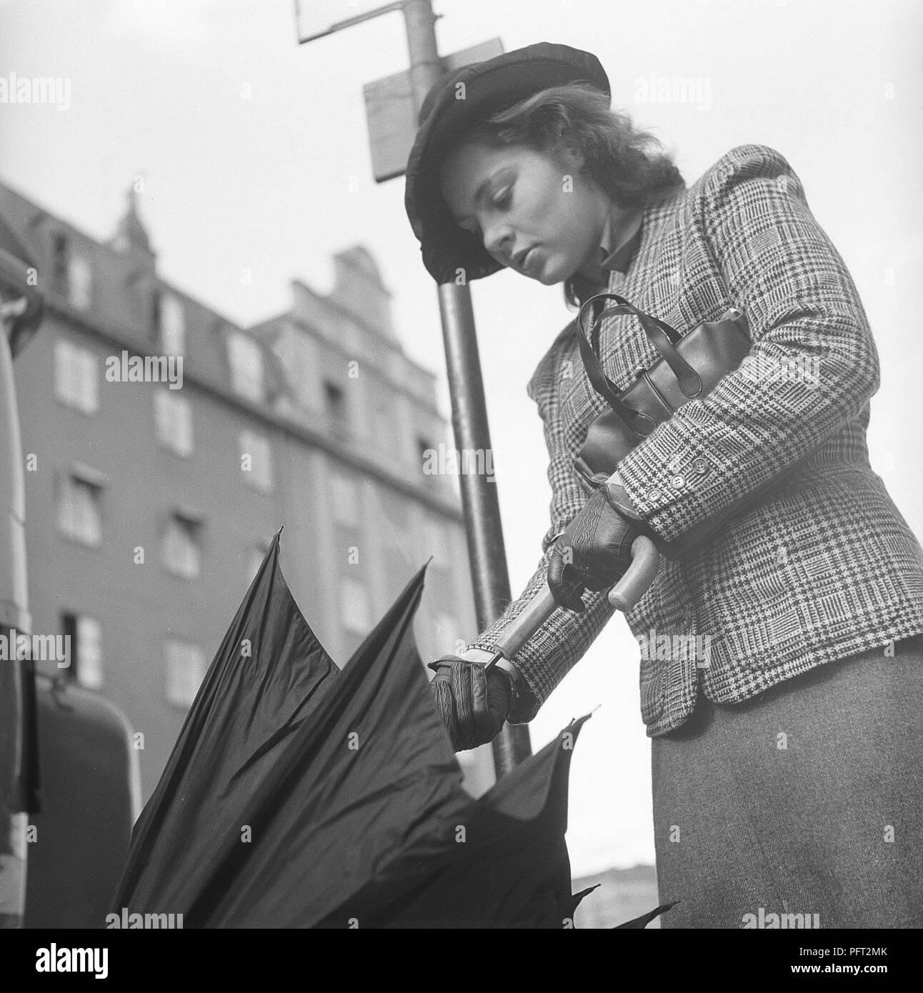 1940s woman in raincoat. Actress Viveca Lindfors, 1920-1995, is waiting at a bus stop and folds her umbrella together when it approaches. She is dressed in 1940s short chequered jacket and skirt, matching hat, handbag and gloves. August 1940. Photo Kristoffersson 159-20 - Stock Image