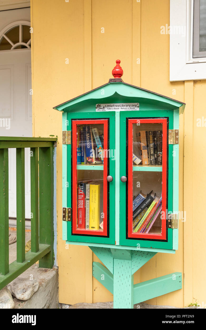 A free library (Take a book - Return a book) outside a house in Juneau the capital city of Alaska, USA - Stock Image