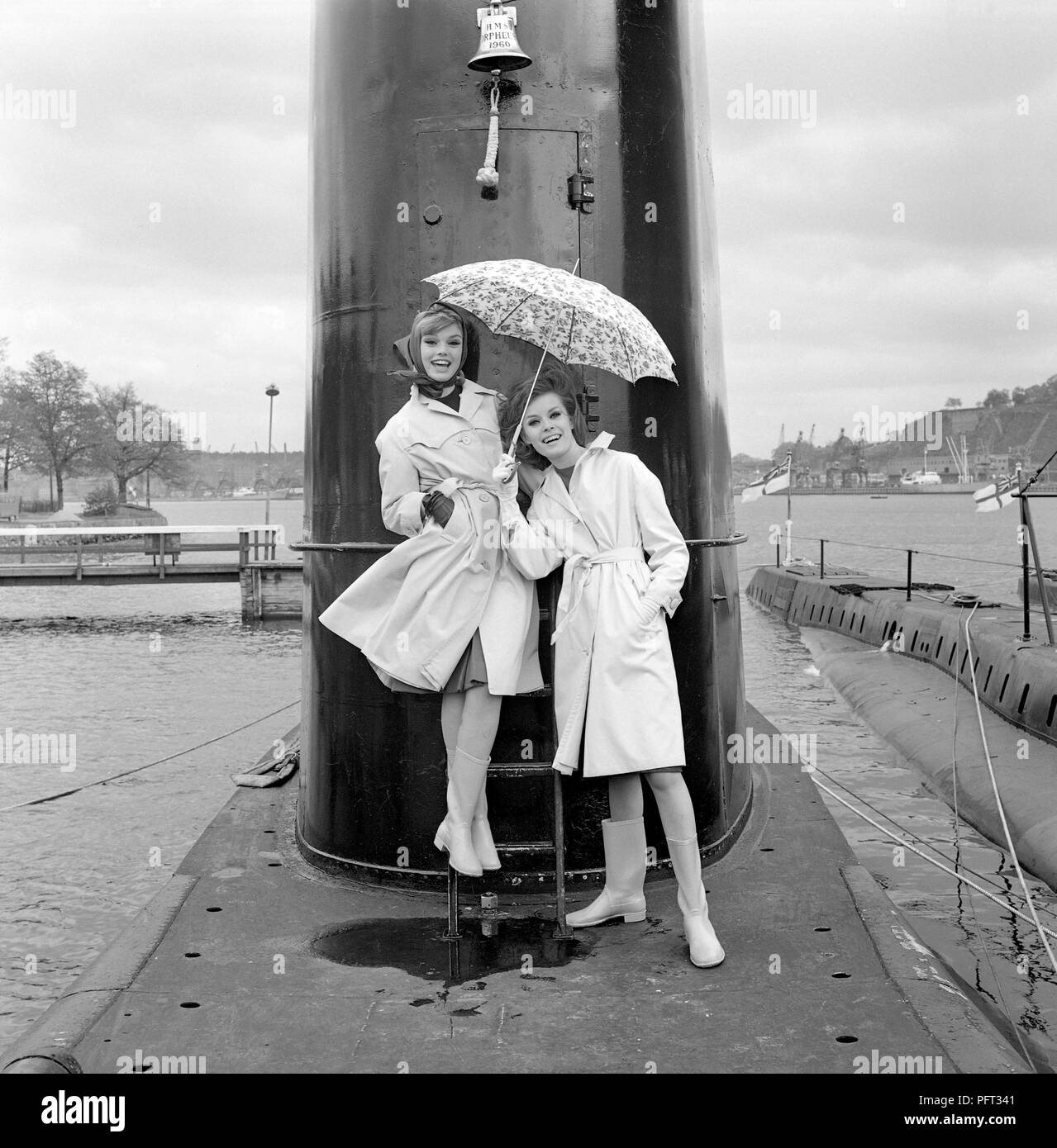 1960s fashion. Two fashion models pictured aboard the British submarine Orpheus. The submarine is anchored in the port of Stockholm. The models are wearing the autumns fashion of raincoats. Sweden May 1962 - Stock Image