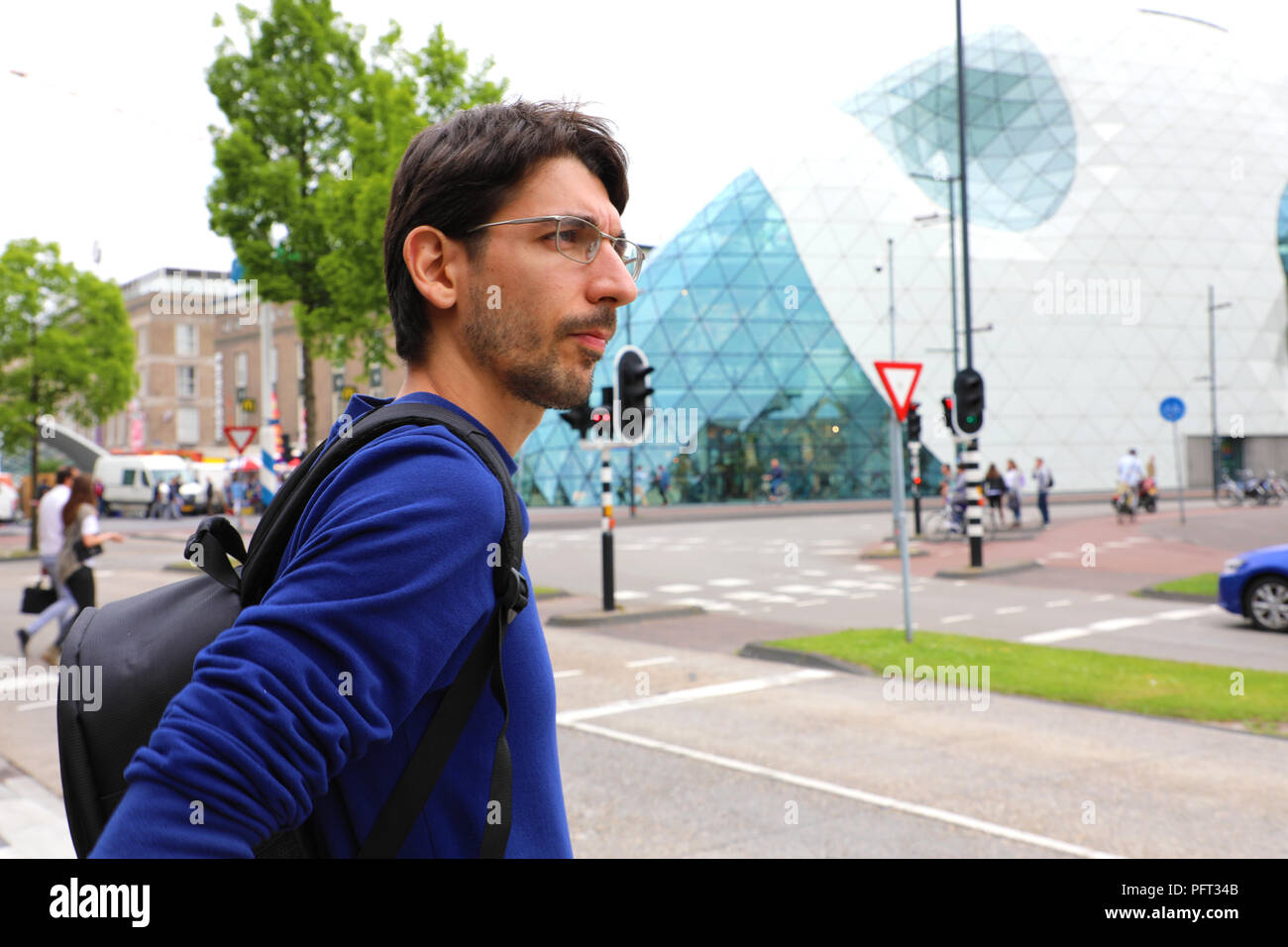 Young man with backpack waiting taxi or bus in Mathildelaan main street in Eindhoven, Netherlands Stock Photo