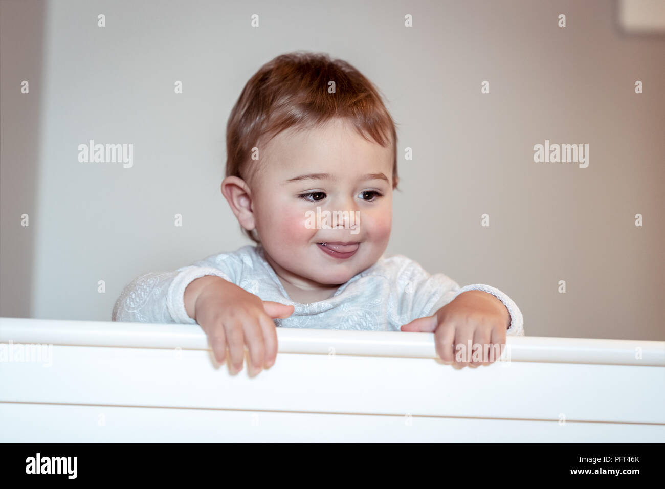 Sweet baby boy standing in his nice white cot, little child in sleepwear in the kidsroom at home, preparing to nap, happy carefree childhood - Stock Image