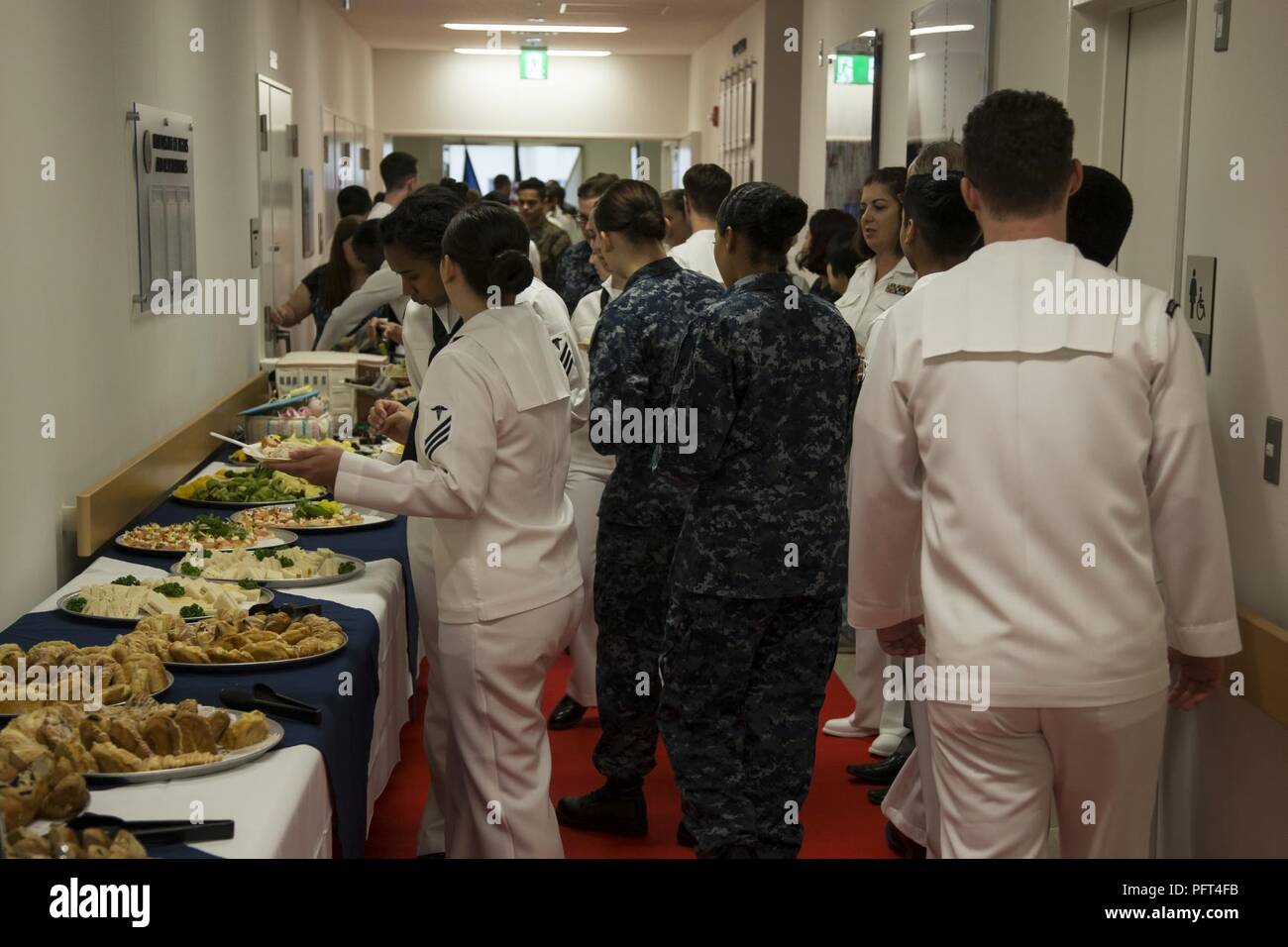 U.S. Service Members gather around a refreshment table during the grand opening of Robert M. Casey Naval Family Branch Clinic Iwakuni at Marine Corps Air Station Iwakuni, Japan, May 30, 2018. The staff hosted the grand opening in order to display the facility's new and improved capabilities. Stock Photo