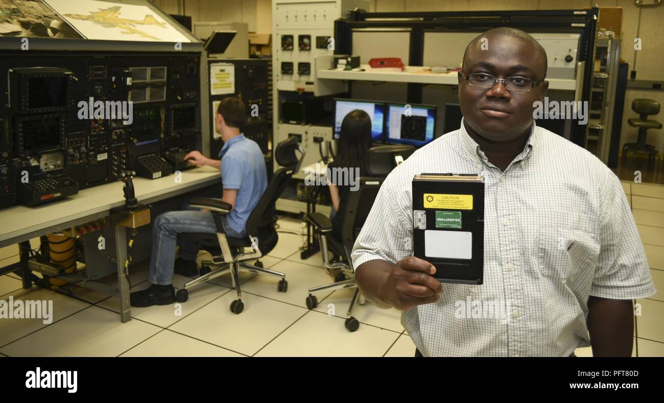 Emmanuel Koomson, 557th Software Maintenance Squadron lead test engineer holds a data transfer cartridge for the B-52H which contains the latest software upgrades developed by his team in the Mission Planning Environment section in the B-52 software test lab on May 29, 2018, Tinker Air Force Base, Oklahoma. Koomson works with Jeff Becker, left, and Nhi Dinh, middle, who are also B-52H MPE electronics engineers with 557th SMXS. - Stock Image
