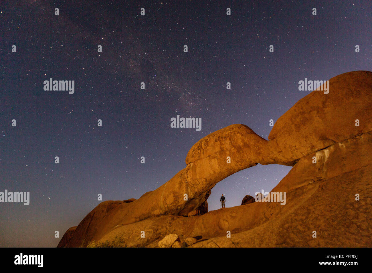 Milky Way shines over an arch in the desert in Namibia - Stock Image