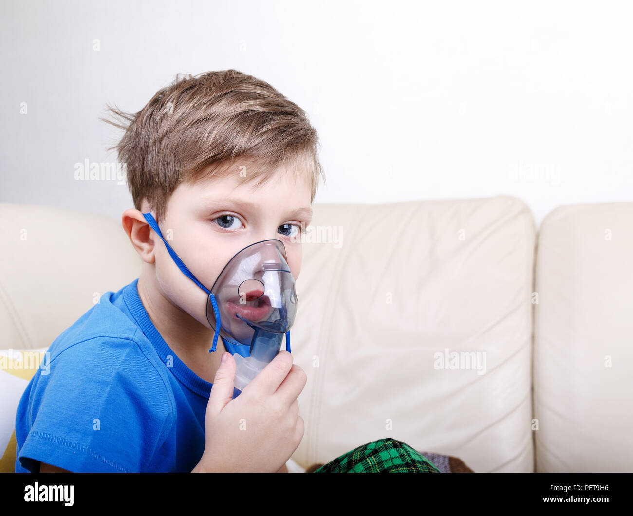 Sick chid with pediatric nebulizer looking at camera - Stock Image