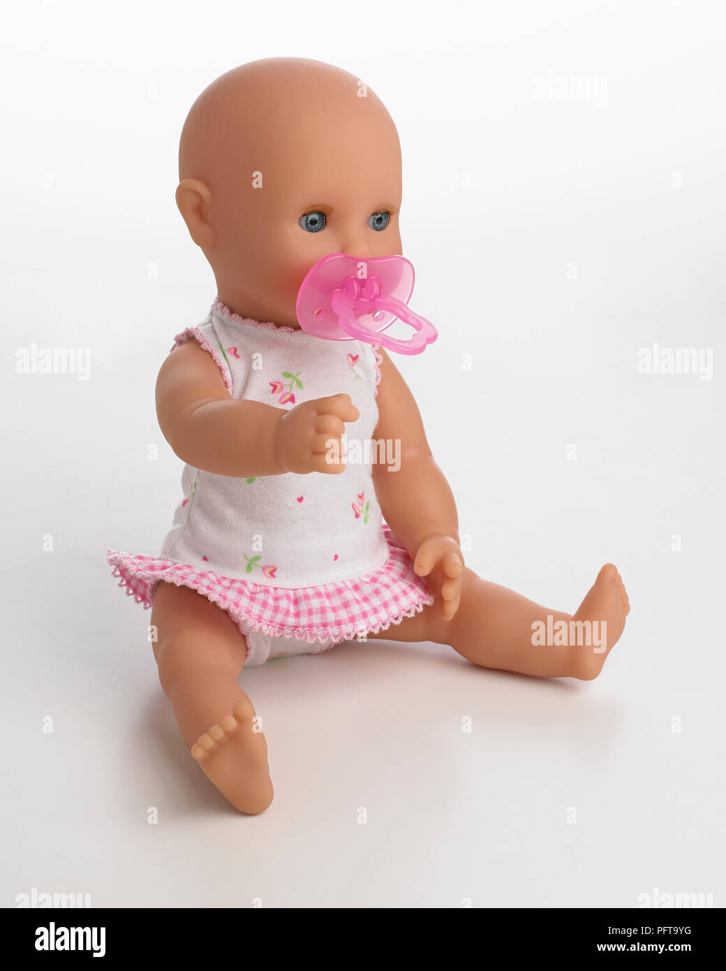 Doll baby with dummy in mouth - Stock Image