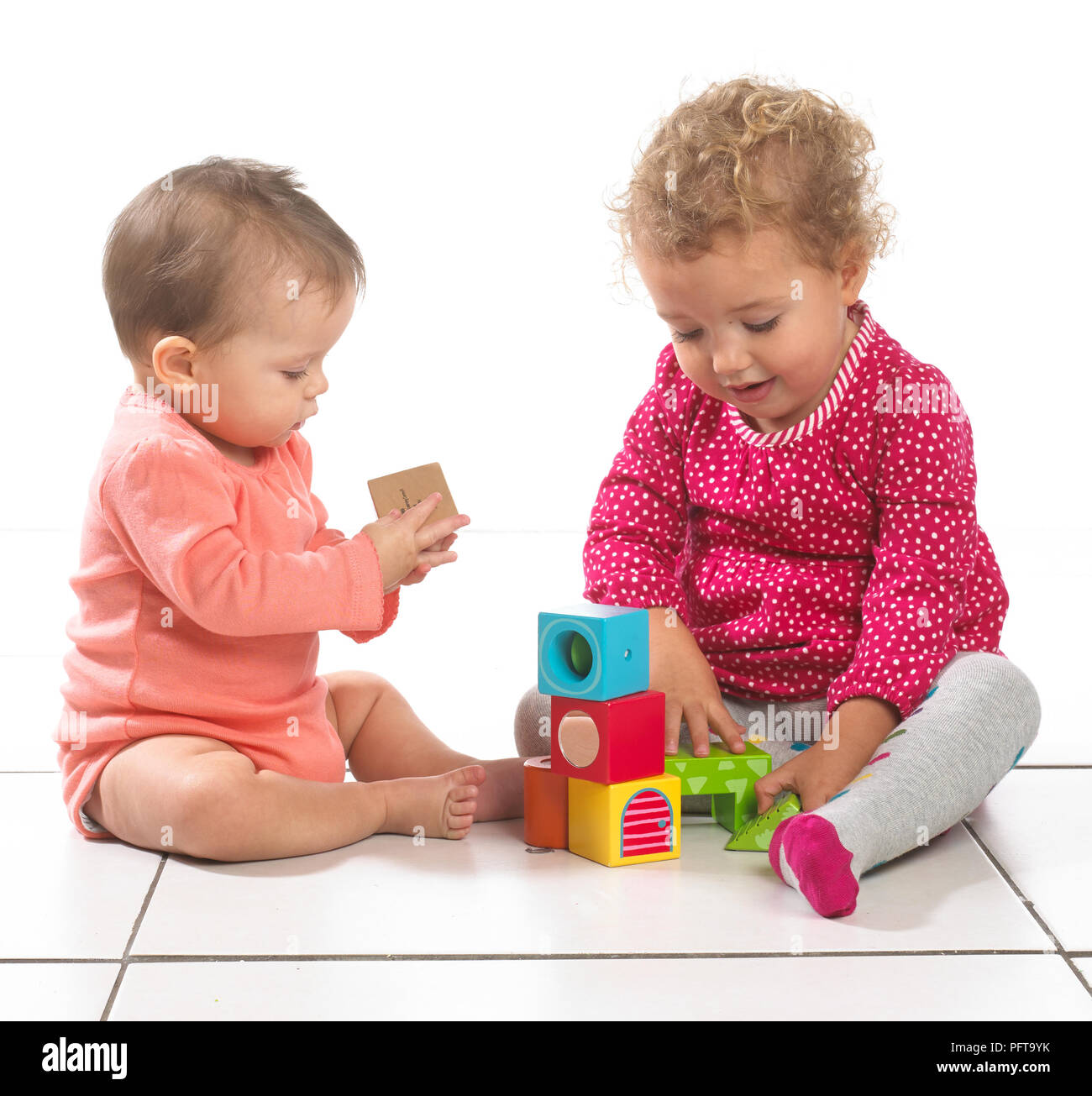 Baby girl (8 months) and toddler girl (2 years) sitting playing with building blocks - Stock Image