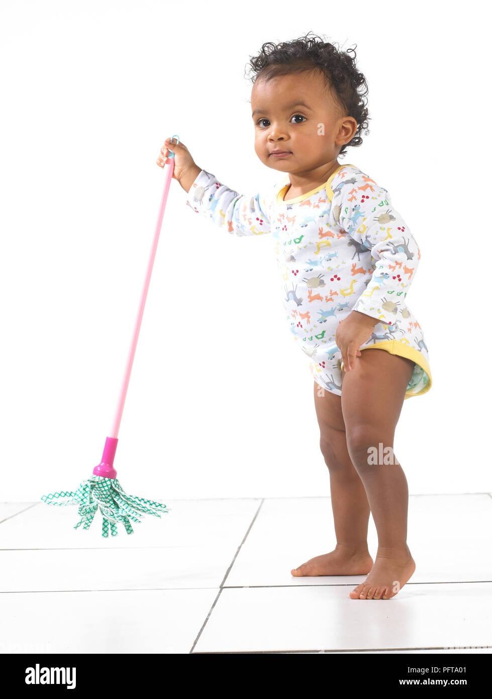 Girl standing holding toy mop, 18 months - Stock Image
