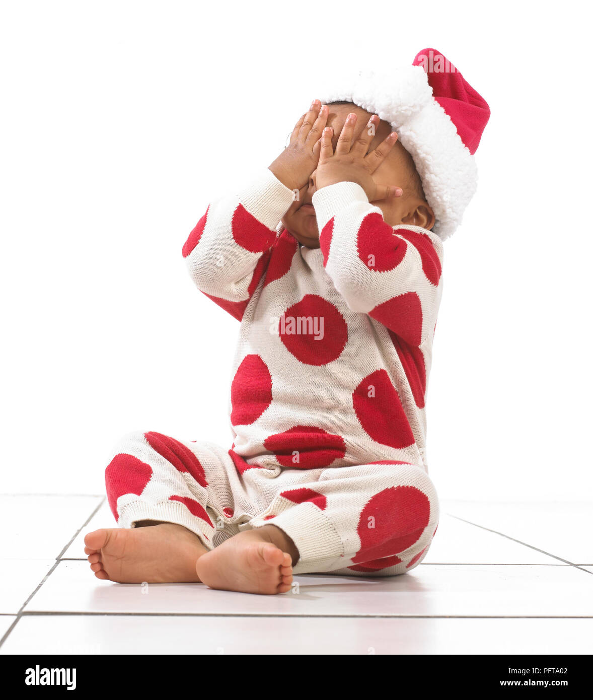 Girl wearing onesie, christmas hat and covering eyes with hands, 18 months Stock Photo