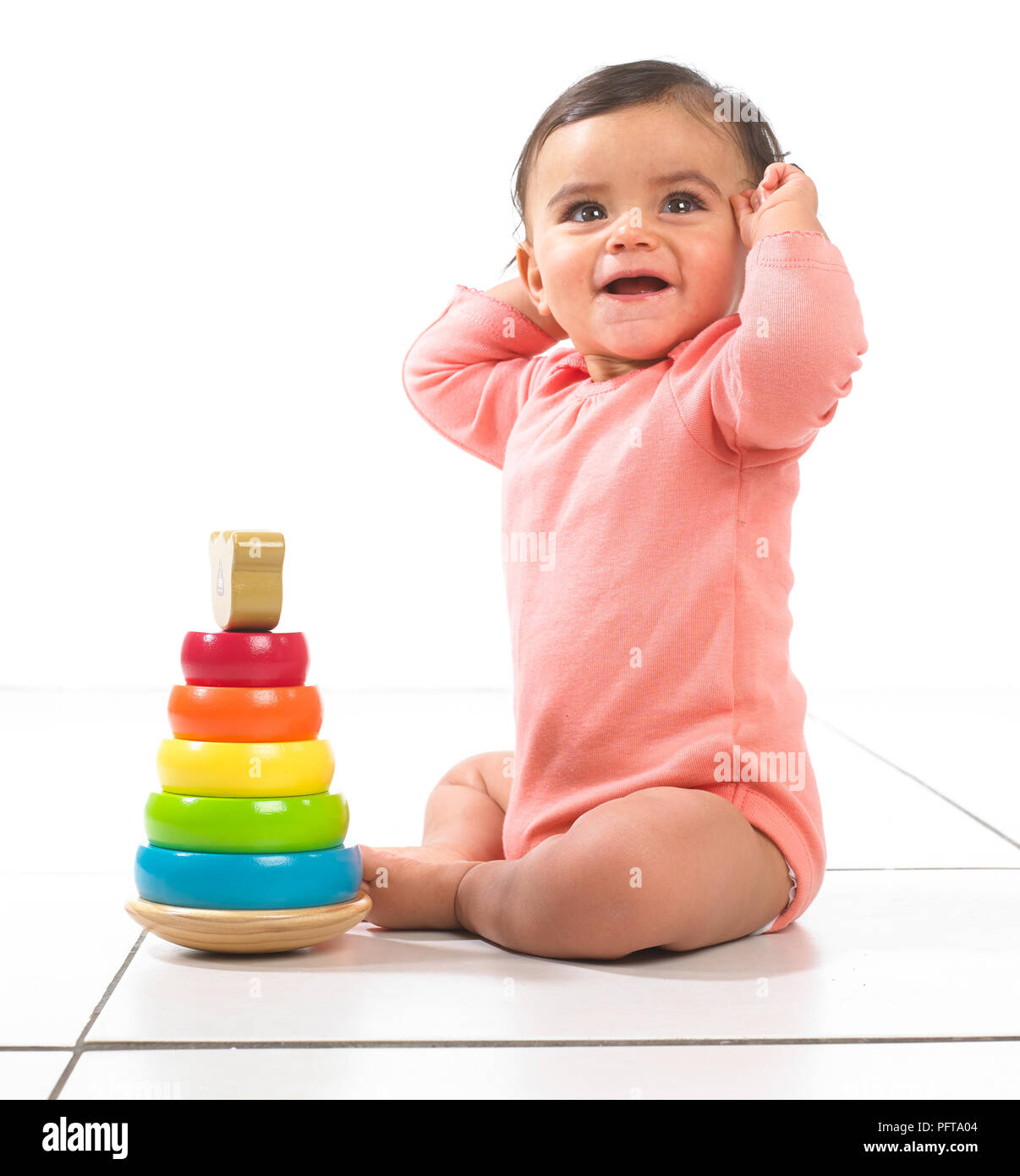 Baby girl sitting playing with stackable ring toy, 7 months - Stock Image