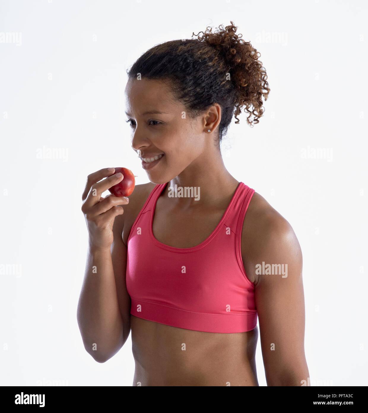 Woman in crop top eating apple - Stock Image