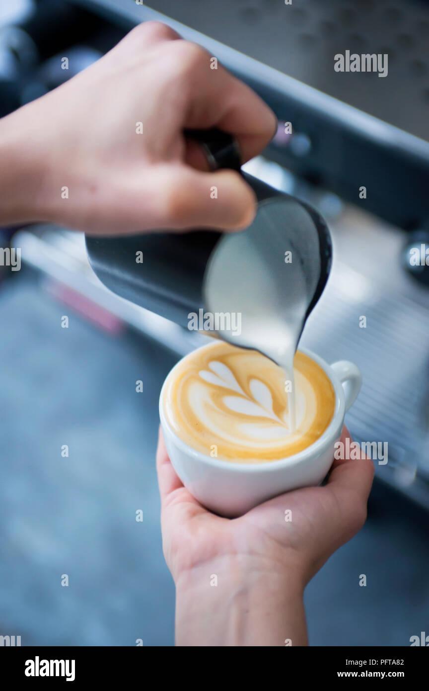 Pouring a Tulip latte art - Stock Image