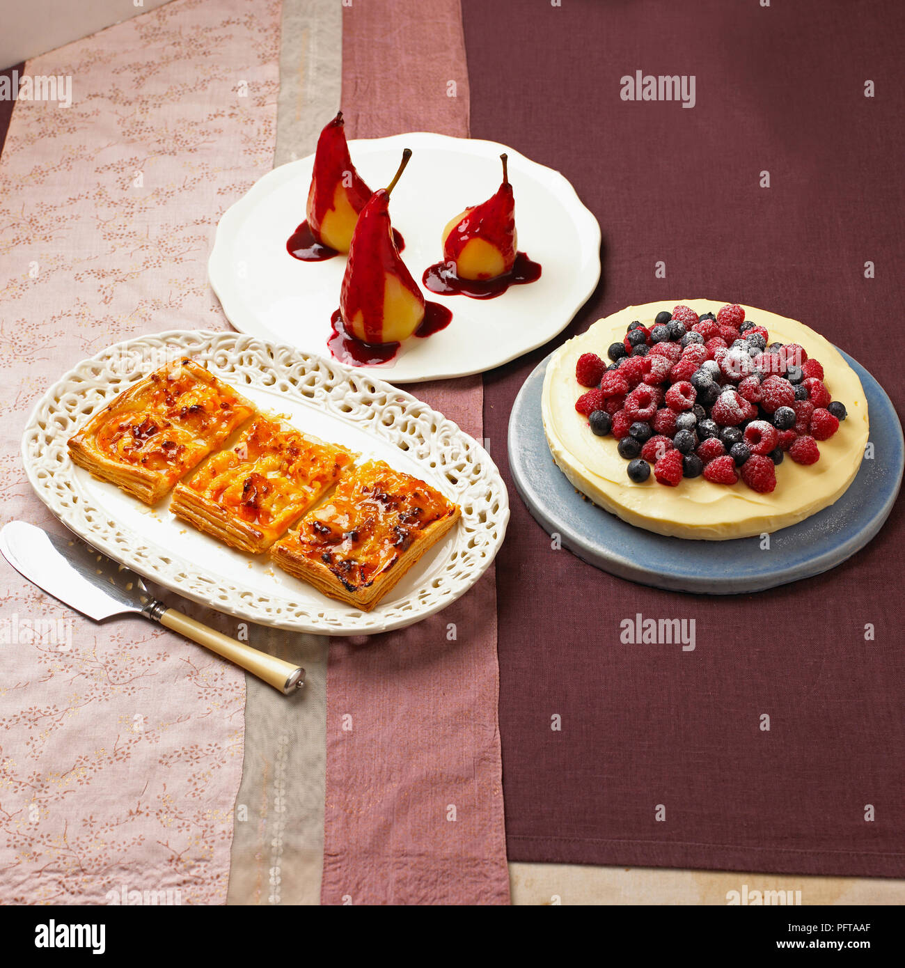 Dessert collection, apricot and almond galette, poached pears with blackberry sauce, lemon cheesecake topped with fresh berries - Stock Image