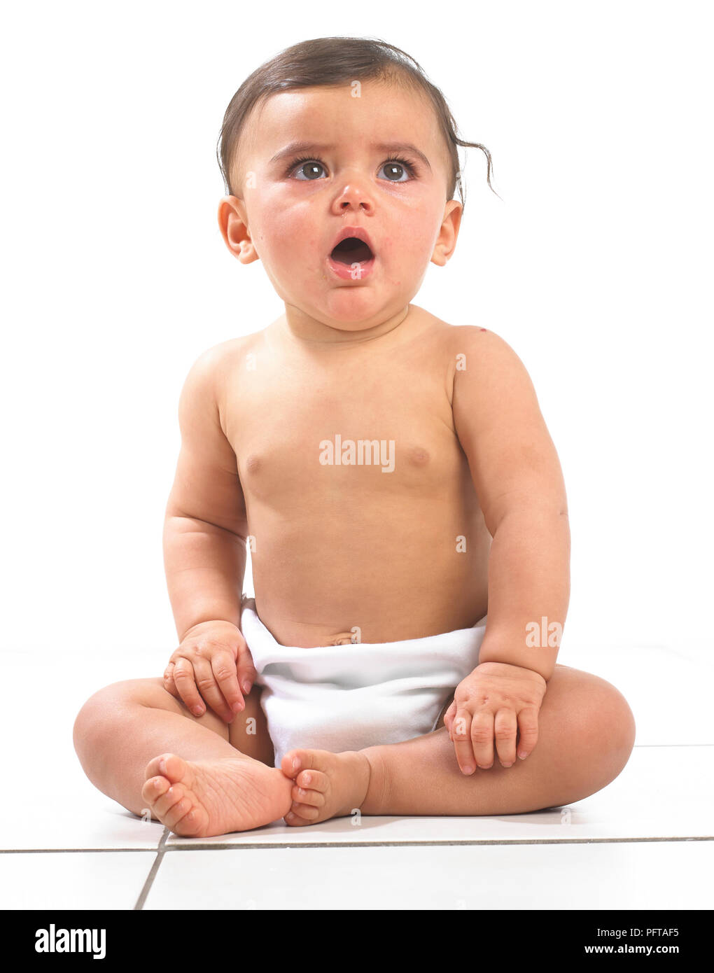 Baby girl sitting wearing nappy, 7 months - Stock Image