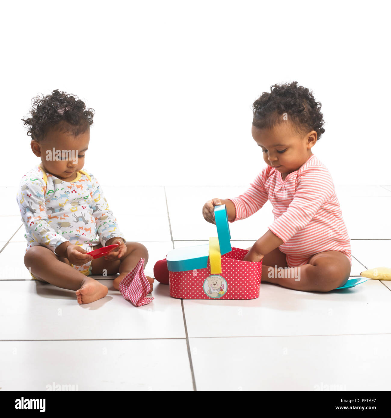 Twin girl and boy sitting playing with toy picnic basket, 18 months - Stock Image