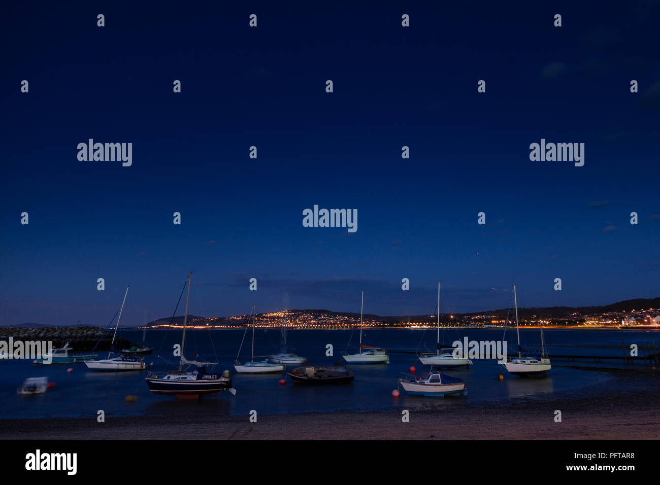 Small boats at night in Rhos-on-Sea harbour on the North Wales coast - Stock Image