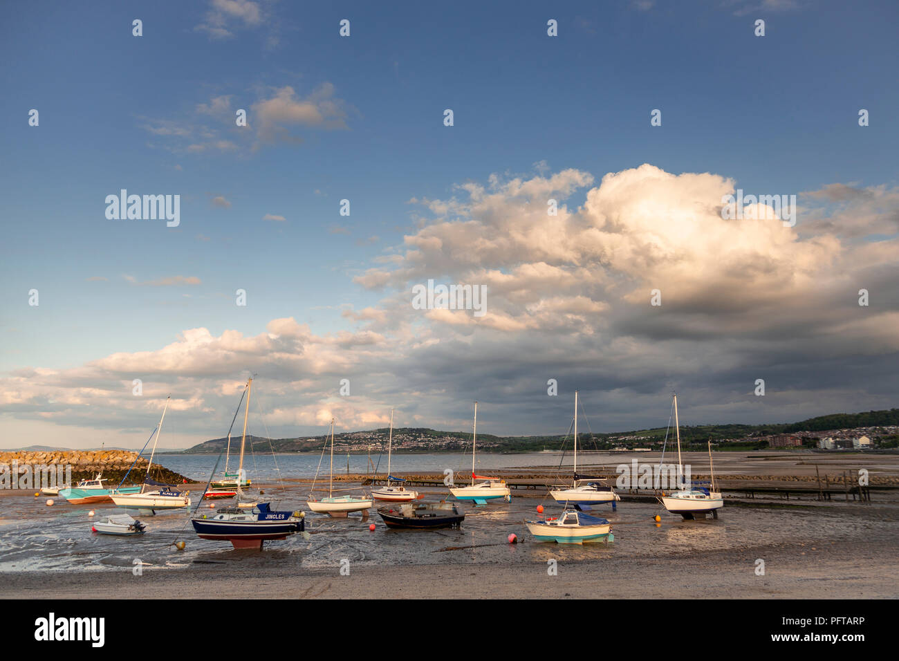 Small boats at low tide in Rhos-on-Sea harbour on the North Wales coast - Stock Image