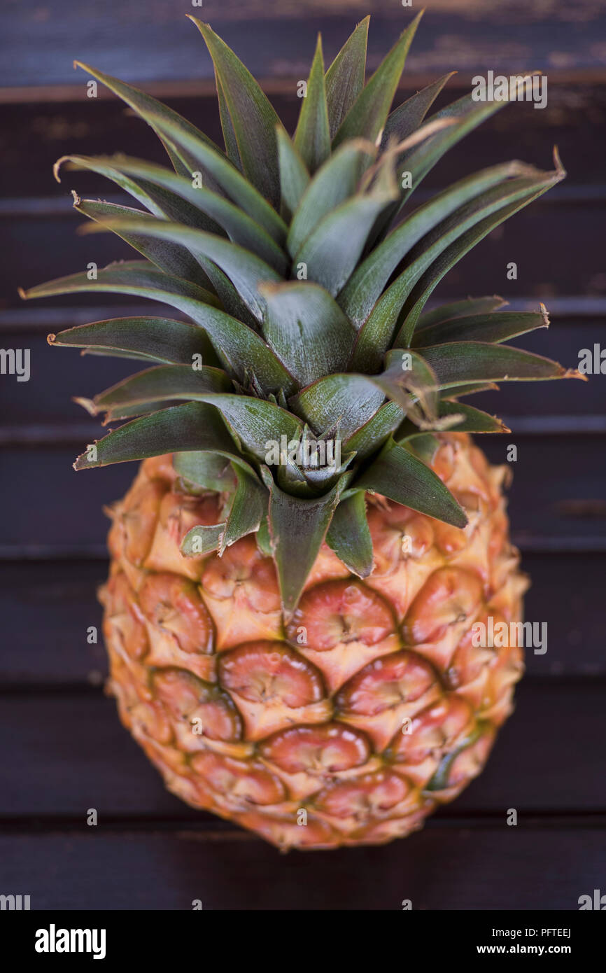 Ripe pineapple, a healthy tropical fruit favorite for its bromelain enzyme and antioxidant characteristics set on a wooden table with selective focus - Stock Image