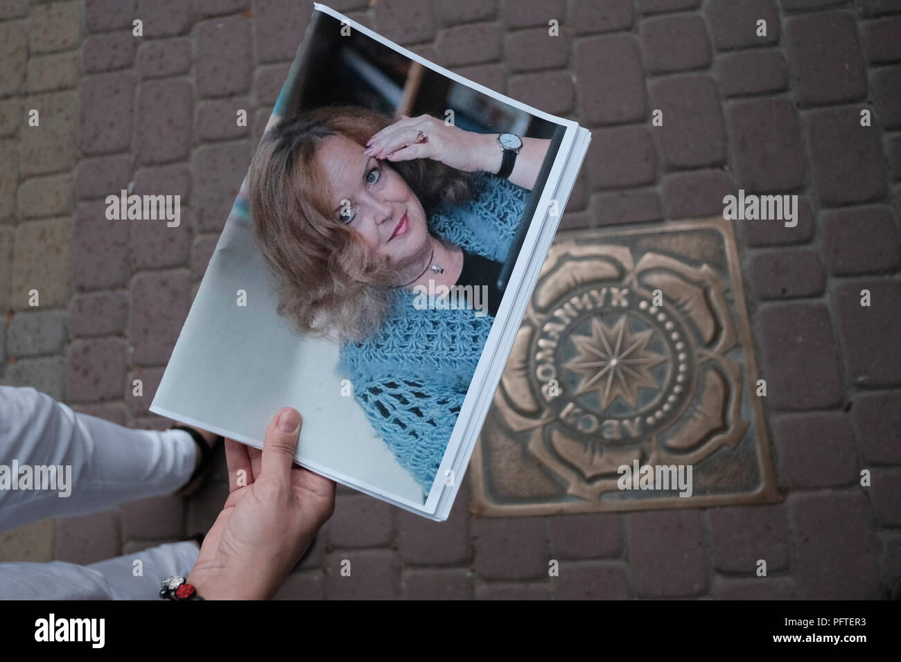 A person holds a photo of Lesia Kokovska Romanchuk an Ukrainian novelist over a brass star embedded in the sidewalk bearing her name in the so called Walk of Fame street in the city of Ternopil, Western Ukraine. Lesia Romanchuk is also an Associate Professor of the Department of Obstetrics and Gynaecology of Ternopil - Stock Image