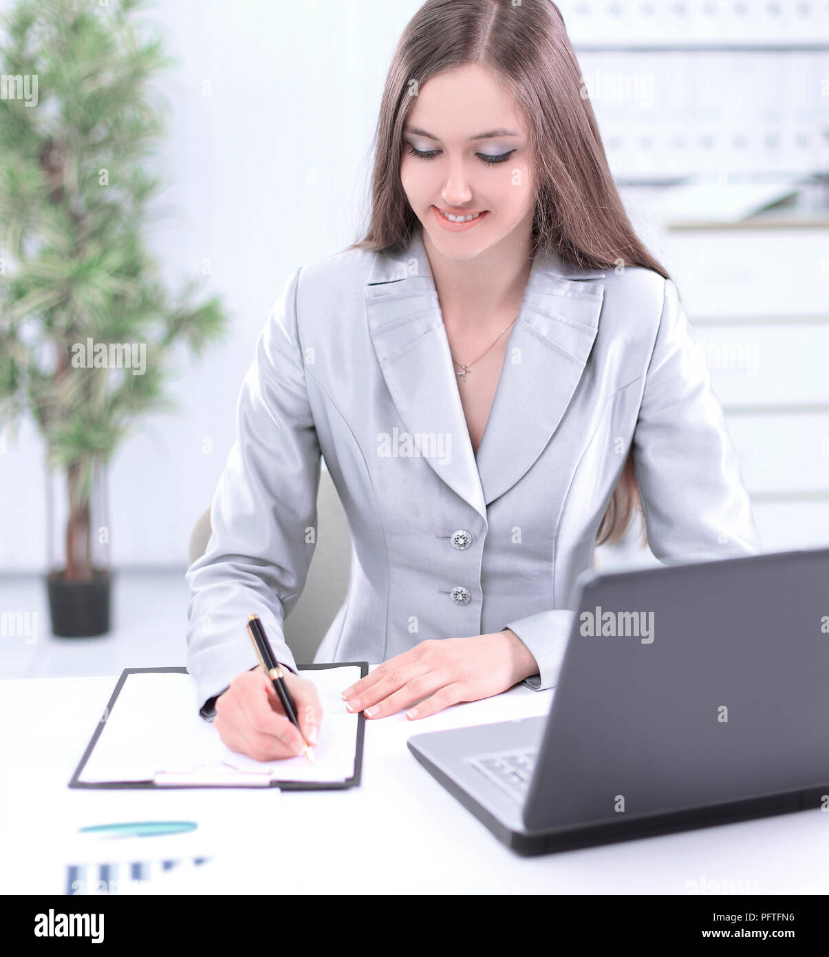 woman assistant making a record on a sheet of paper. - Stock Image