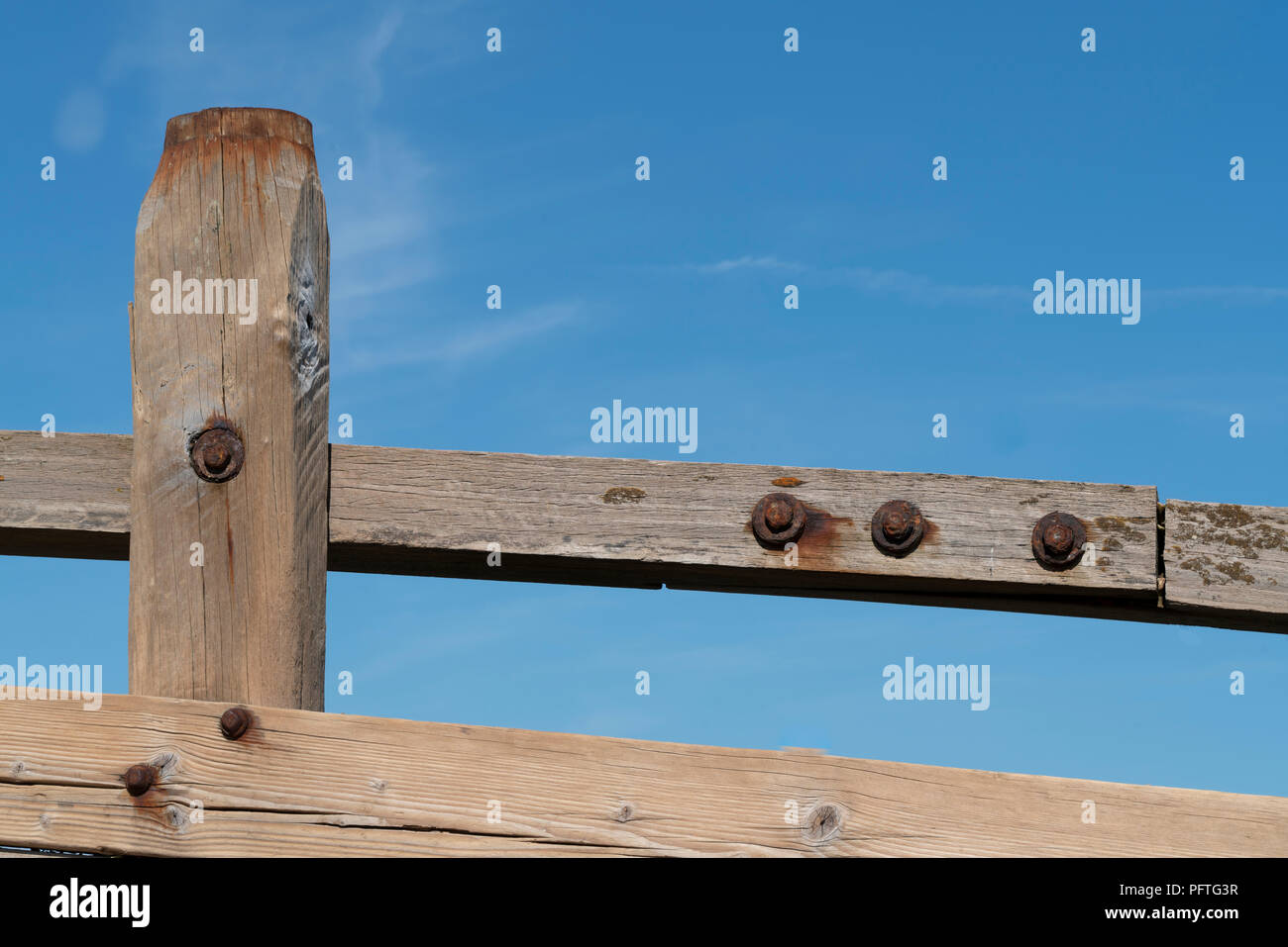 Wooden groyne or sea defence held together with rusting bolts, seen against a clear blue sky with hints of wispy cloud. - Stock Image