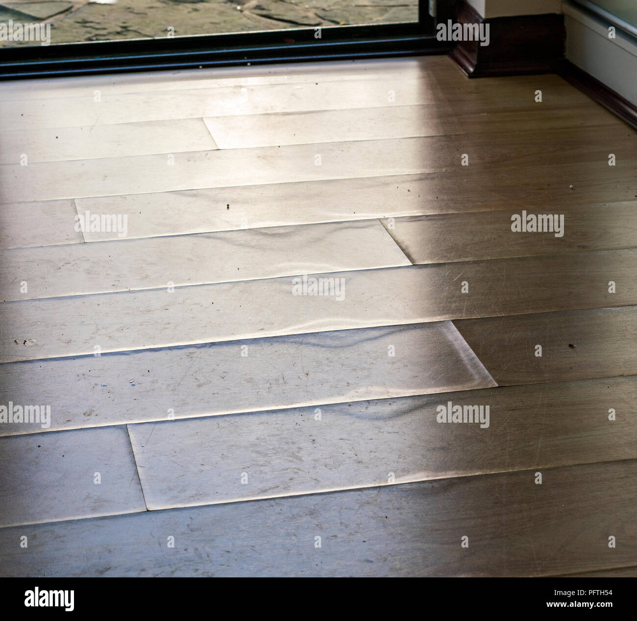 Laminate flooring swollen and delaminated at the edges after prolonged contact with water after a pipe burst. - Stock Image