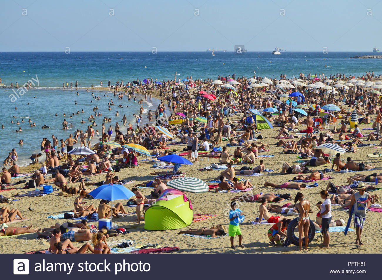 Crowded beach of Barceloneta, holidaymakers by the Mediterranean sea on hot summer day in Barcelona Spain Europe. - Stock Image