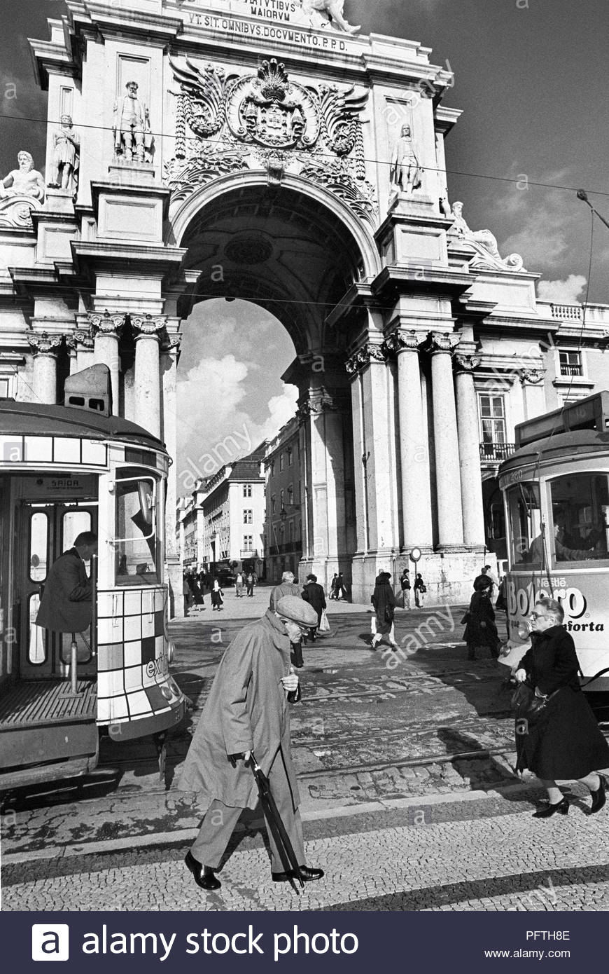 A hunched old man in overcoat and cloth cap, walks past trams in the Praça do Comércio in Lisbon, Portugal. Towering above is the Rua Augusta Arch - Stock Image