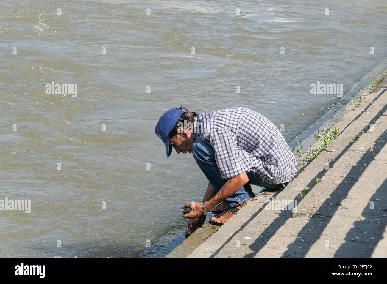 man collecting algae to use as fishing bait from the Vardar River