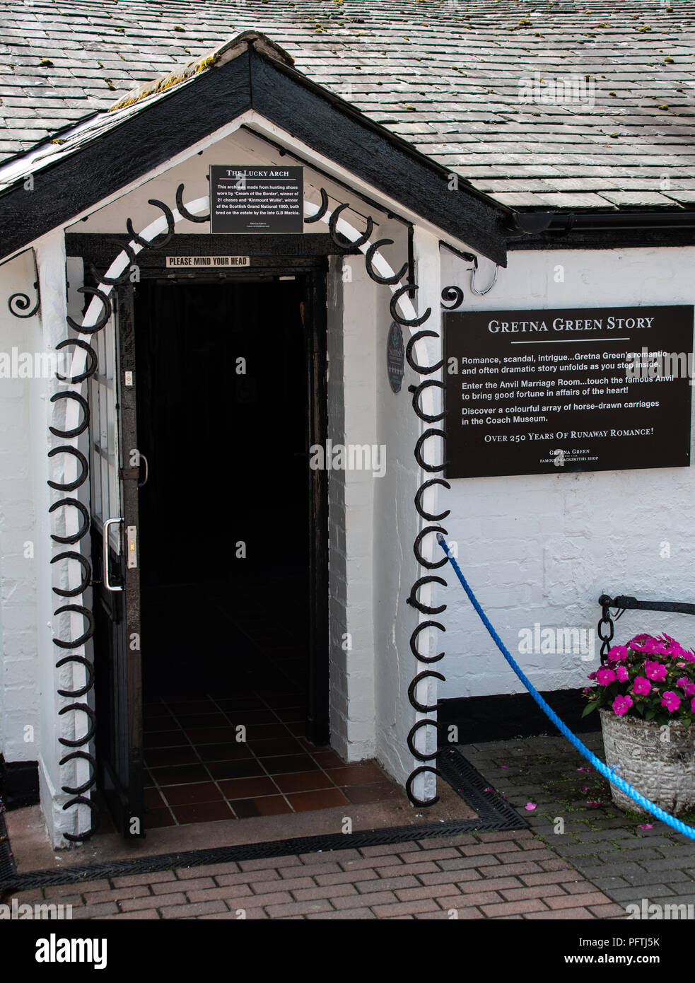 Gretna Green, United Kingdom - August 08 2018:   A doorway decorated with horseshoes for good luck, used by couples getting married at Gretna Green's  - Stock Image