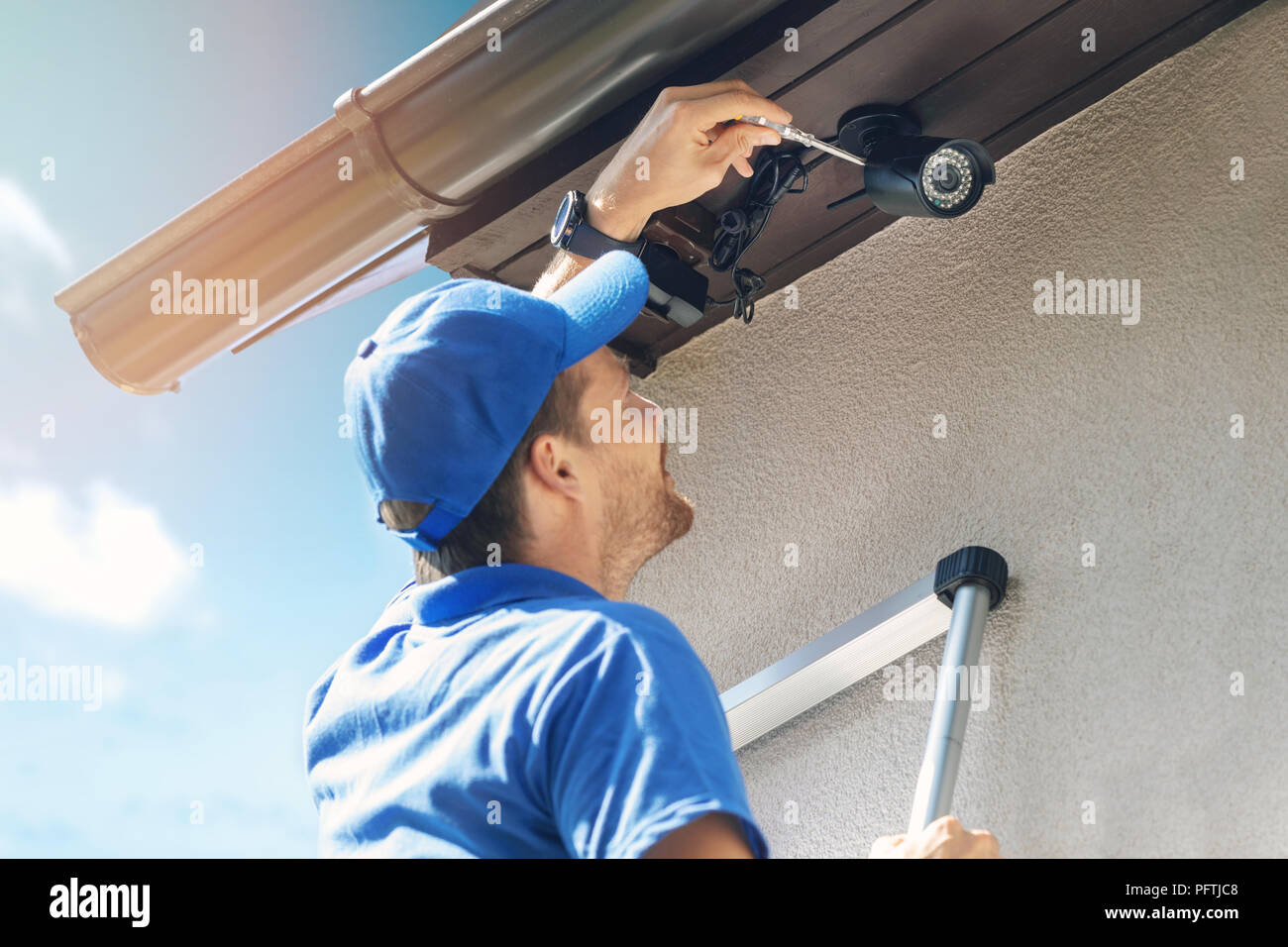 man install outdoor surveillance ip camera for home security - Stock Image