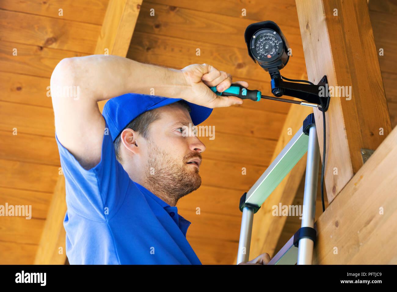 technician installing surveillance camera in the house carport - Stock Image