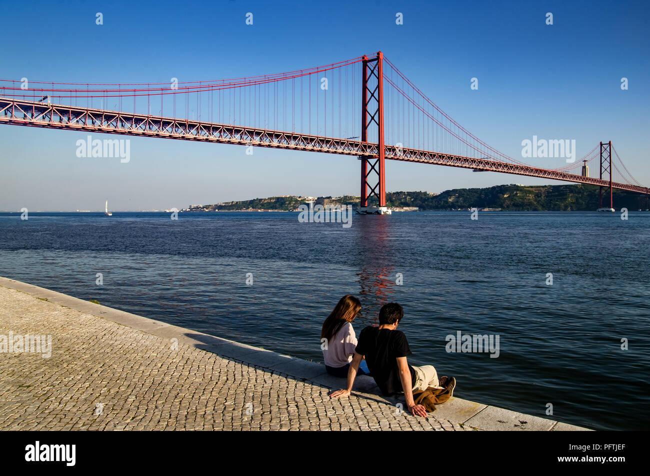 Couple sat near 25 de Abril Bridge, Lisbon, portugal Stock Photo
