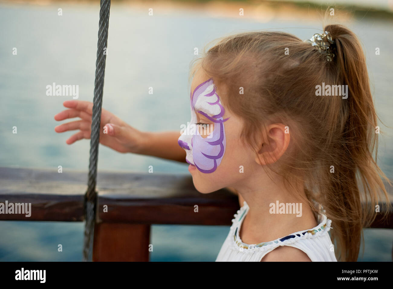 Pretty exciting blue-eyed girl of 5 years with a pink face painting - Stock Image