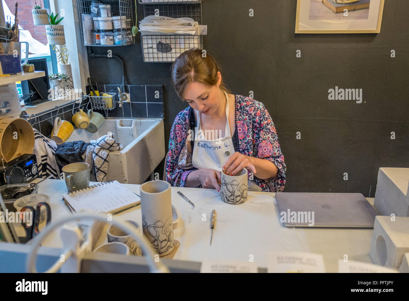 A young lady working in her workshop making ceramic jugs - Stock Image