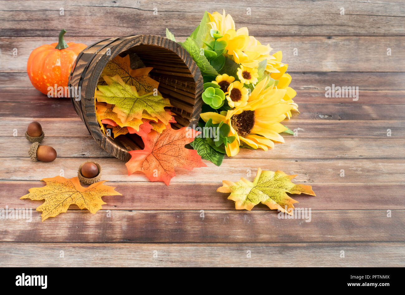 Sunflower bouquet, pumpkin, acorns and a rustic wooden plant pot filled with colorful autumn leaves on brown wood panels. - Stock Image