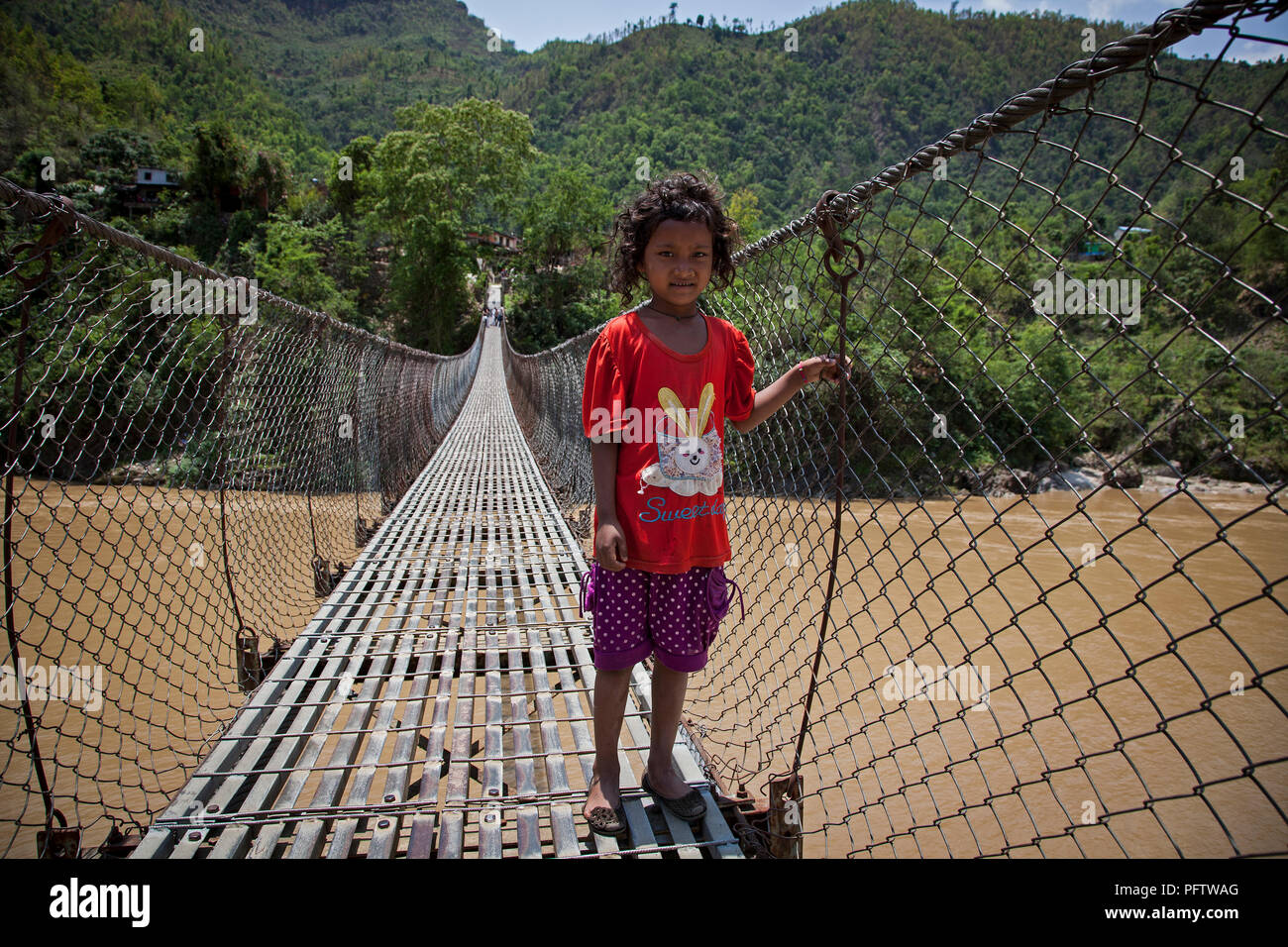 Kid crossing tibetan bridge. Pokhara. Annapurna trek. Nepal - Stock Image
