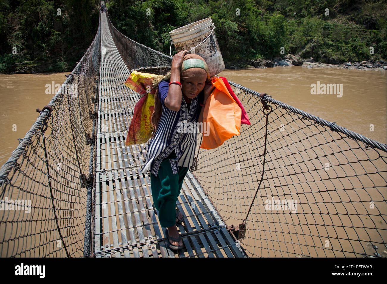 Woman crossing suspension  bridge. Pokhara. Annapurna trek. Nepal - Stock Image