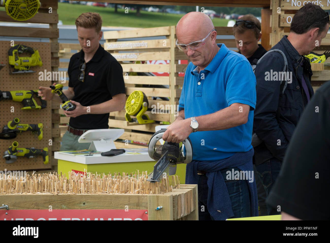 People looking at power tools for sale & man using cordless hedge trimmer - Ryobi trade stand, RHS Chatsworth Flower Show, Derbyshire, England, UK. - Stock Image