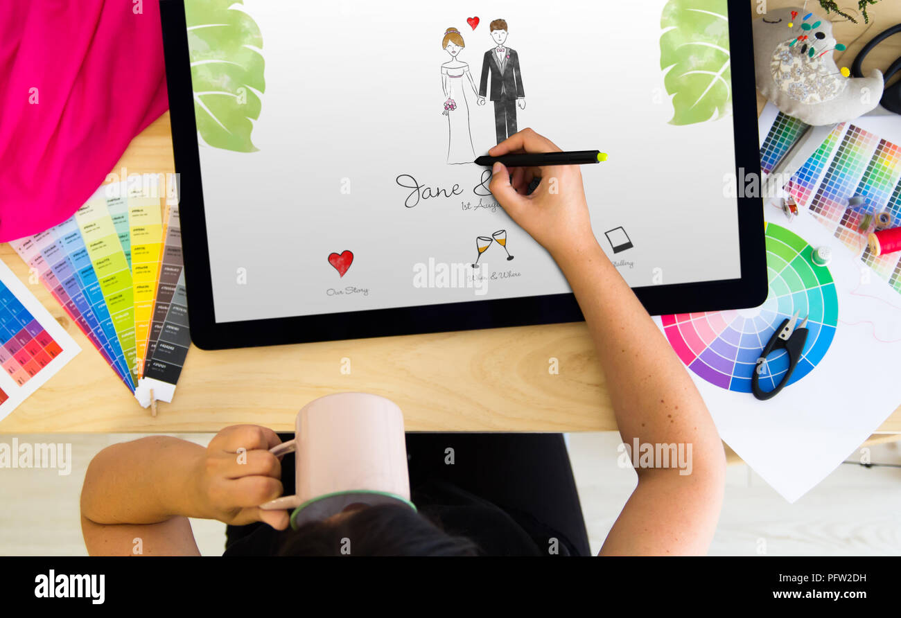 Designer working on wedding invitation with a tablet and a pen. All screen graphics are made up. - Stock Image