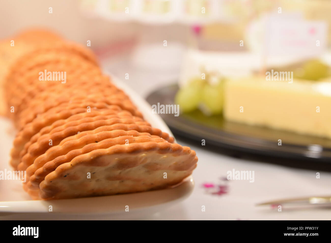 Crisp crackers on a long white dish with cheese and grapes out of focus on a table behind. Party buffet set up with very shallow depth of field - Stock Image